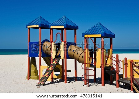 Kids Playground Equipment on a Sandy Beach with Ocean Background