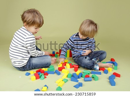 Kids playing a game with blocks, sharing, getting along, and teamwork concepts - stock photo