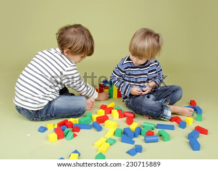 Kids playing a game with blocks, sharing, getting along, and teamwork concepts