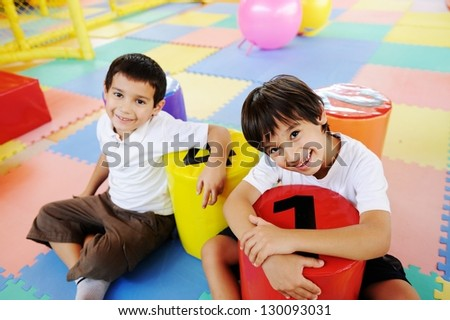 Kids playing at new playground kindergarten with little number chairs - stock photo