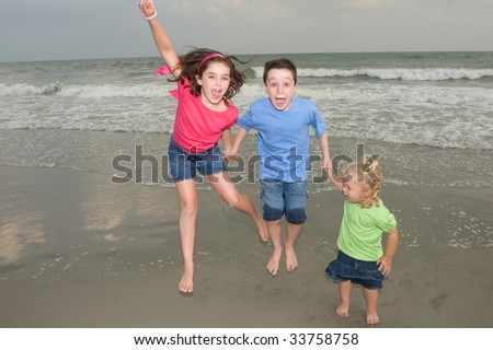 Kids Playing at the Beach - stock photo