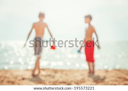 kids playing at the beach, defocused image - stock photo