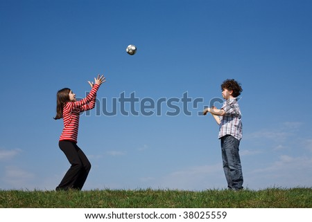 Kids playing ball outdoor against blue sky - stock photo
