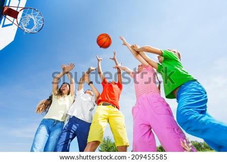 Kids playing basketball with a ball up in sky - stock photo