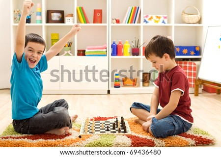 Kids playing chess - one of them just captured a pawn and celebrates - stock photo