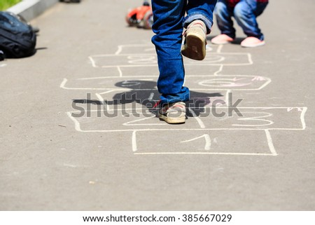 kids playing hopscotch on playground outdoors - stock photo