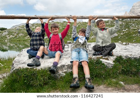 Kids playing in the mountains lifting club. Dolomites, Italy. - stock photo