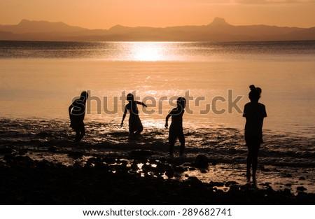 Kids playing in the ocean in Savusavu, Fiji at sunset - stock photo