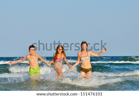 kids  playing  in water against the waves - stock photo