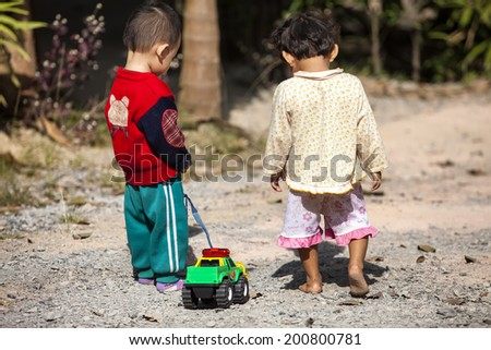 Kids playing naughty with toys trucks. - stock photo
