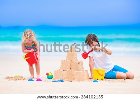 Kids playing on a beach. Two children build a sand castle at the sea shore. Family vacation on a tropical island. Boy and girl digging with toy spade and kid spade. Traveling with young child. - stock photo