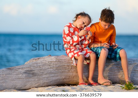 Kids playing on a portable game device or smartphone at beach