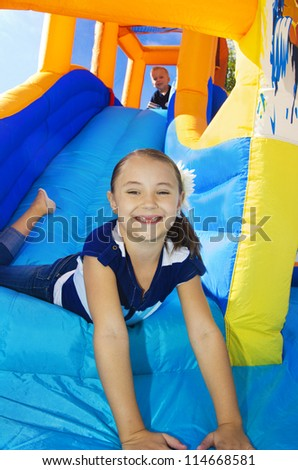 Kids playing on an inflatable slide bounce house - stock photo