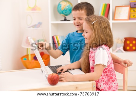 Kids playing on laptop computer at home together - stock photo