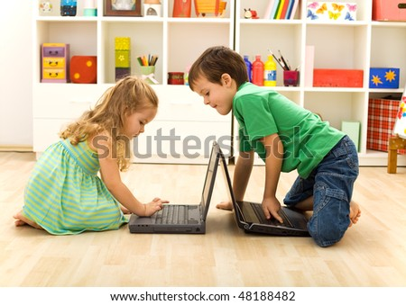 Kids playing on laptops - boy teaching little girl what key to press