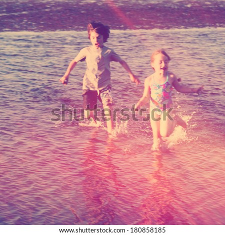 Kids playing on the beach in water - Instagram effect - stock photo
