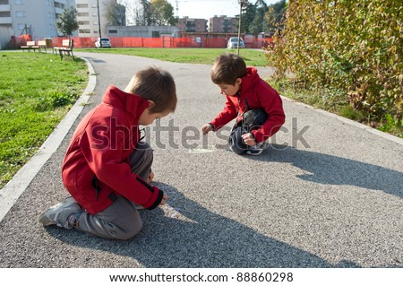 Kids playing on the ground with chalk. - stock photo