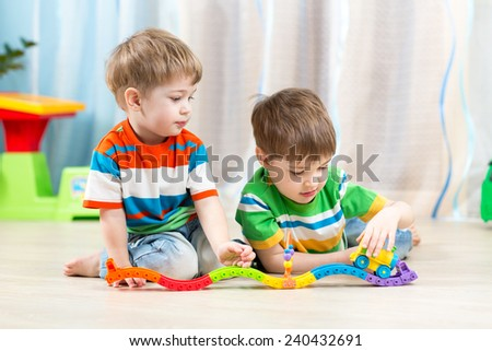 kids playing rail road toy in nursery - stock photo