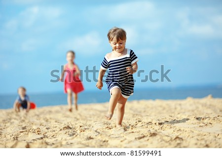 Kids playing running on sand at the beach - stock photo