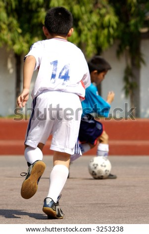 Kids playing soccer. - stock photo