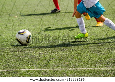 Kids playing soccer, unrecognizable boy running for soccer ball - stock photo