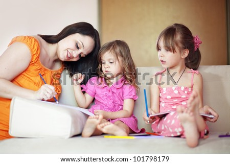 Kids playing together with their mother at home - stock photo