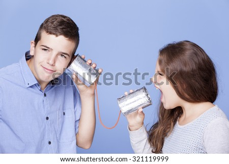 Kids playing with a can as a telephone on blue background - stock photo