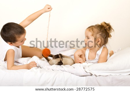 Kids playing with a yarn ball and a kitten on the bed