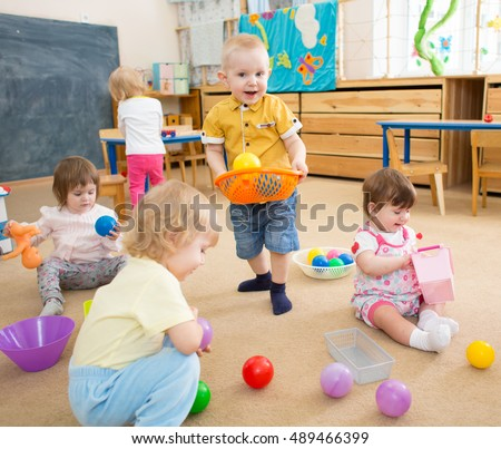 kids playing with balls in kindergarten room
