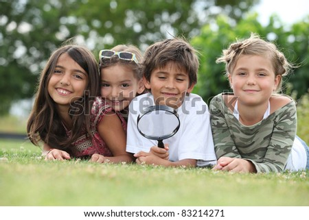 Kids playing with magnifying glass in park - stock photo