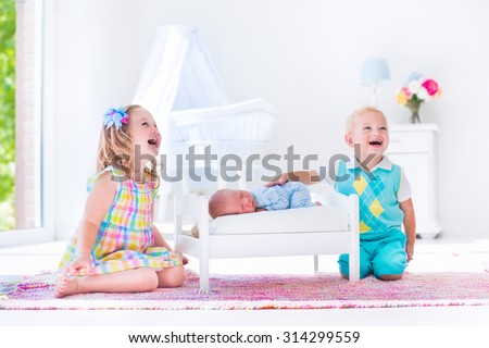 Kids playing with newborn baby brother. Toddler and preschooler girl play with new born boy in toy bed. Nursery interior and textile bedding. Children meet infant sibling. White bedroom with bassinet. - stock photo