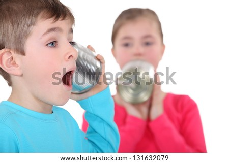 Kids playing with tin cans - stock photo