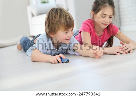 Kids playing with toy cars laying on floor - stock photo