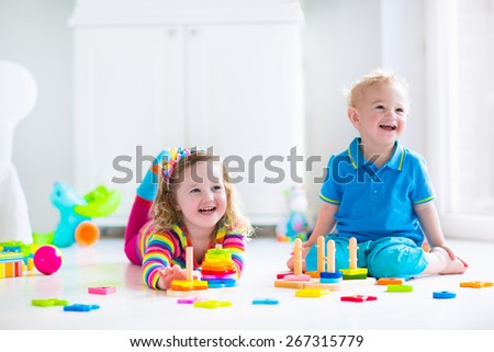 Kids playing with wooden toys. Children, cute toddler girl and funny baby boy, playing with toy blocks, building towers at home or day care. Educational child toys for preschool and kindergarten. - stock photo