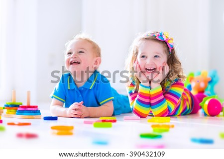 Kids playing with wooden toys. Two children, toddler girl and funny baby boy, playing with wooden toy blocks, building towers at home or day care. Educational child toys for preschool and kindergarten - stock photo