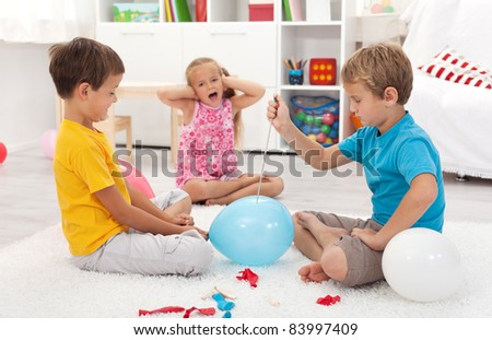 Kids popping balloons in their room fearing the blast - focus on the right side boy