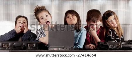 Kids posing as a professional business team making funny faces - stock photo