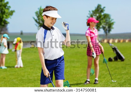 Kids practicing hits at golf school at summer day - stock photo