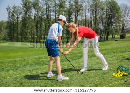 Kids practicing with trainer at golf school at summer day - stock photo