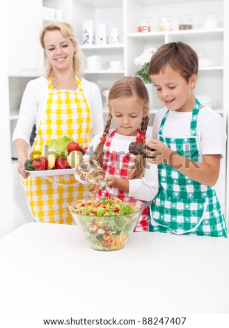 Kids preparing and seasoning a healthy fresh salad in the kitchen - stock photo