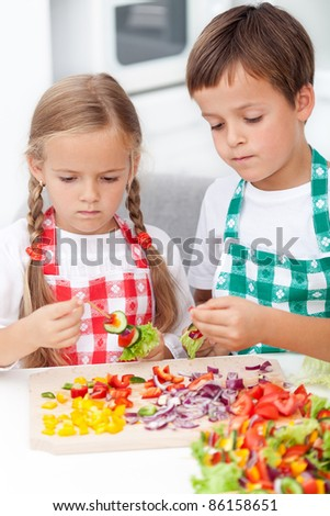 Kids preparing veggies on stick in the kitchen - healthy nutrition concept