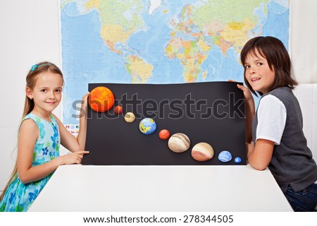 Kids presenting their science home project - the planets of our solar system-focus on the girl face - stock photo