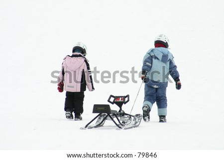 Kids pulling a sled - stock photo