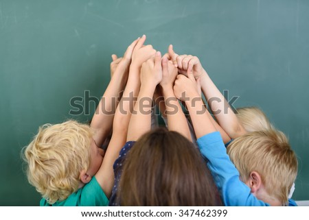 Kids Raising their Arms at the Center together and Showing Thumbs Up Hand Signs Against Green Chalkboard. - stock photo