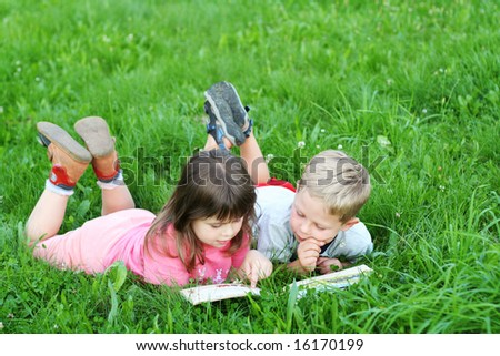 Kids reading a book on grass - stock photo