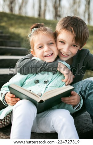 Kids reading together enjoying a book outdoors - stock photo