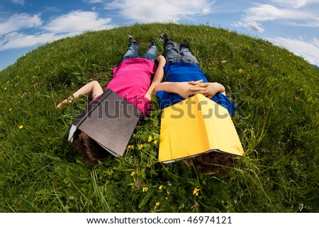 Kids relaxing on green meadow - stock photo