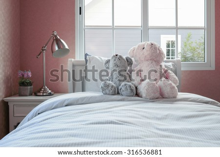 kids room with dolls and pillows on bed and bedside table lamp - stock photo
