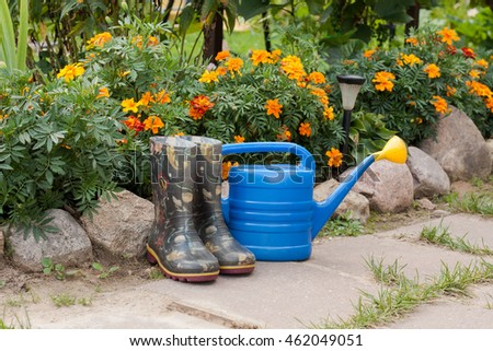 Kids rubber boots and a blue watering can in the garden.
