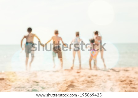 kids running at the beach, defocused image - stock photo
